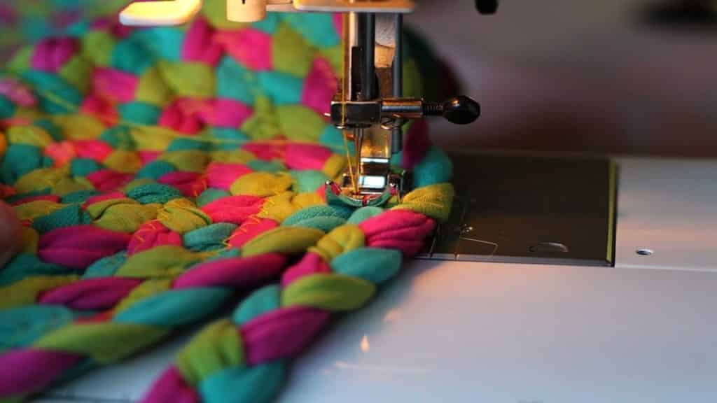 A multi-colored fabric being stitched by a sewing machine